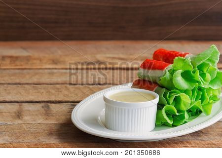 Fresh spring rolls with fresh vegetable and crab stick served with spicy salad cream dipping sauce. Rolls salad or fresh spring roll on white plate healthy delicious food for appetizer or meal. Fresh spring rolls in fusion food style.