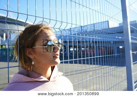 Urban lifestyle fashion portrait of trendy-looking European teenage girl wearing srtylish round sunglasses and pink hoodie posing outdoors at fence netting enjoying sunny weather on summer day