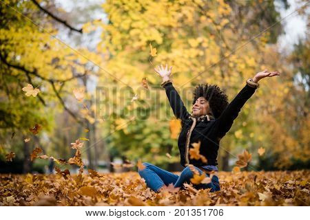 Happy young woman sitting on autumn leaves in park