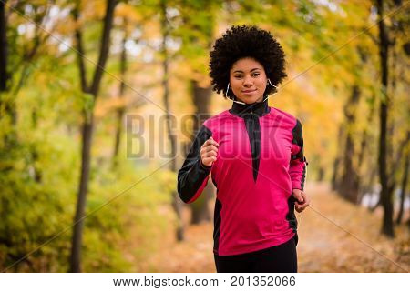 Sporty woman listening to music while running outdoors