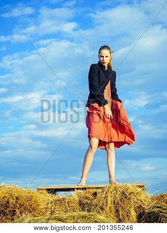 Woman relaxing on nature. Girl posing on hey on blue sky. Summer vacation and wanderlust. Fashion and accessories concept. Model in red tie and skirt.