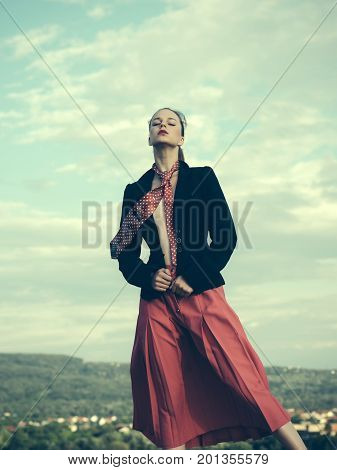 Model in red tie and skirt vintage filter. Fashion and accessories concept. Girl posing on natural background. Summer vacation and wanderlust. Woman relaxing on nature.