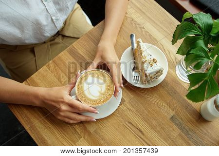 cup of coffee in a cafe and a girl's hands. Close-up of woman's hands sitting with cup of coffee in a cafe.