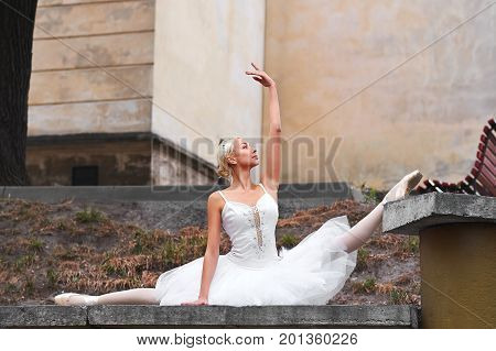 Gorgeous blonde haired ballerina doing splits while performing outdoors in the city flexible flexibility balance athletics beauty grace.