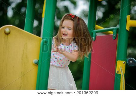 The charming little girl plays in the jungle gym. To the child it is very cheerful.
