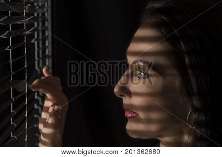 Portrait of a woman standing in the dark looking through blinds