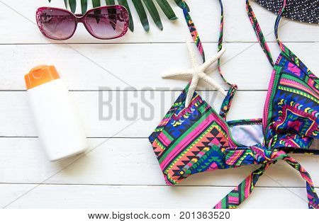 Summer Fashion woman swimsuit Bikini camera fish star sunblock sun glasses hat on white wood. Travel in the holiday. Summer Concept.