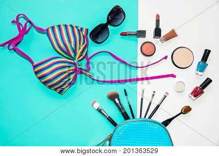 Cosmetics and fashion background with make up artist objects: lipstick eye shadows mascara eyeliner concealer nail polish with summer bikini. Lifestyle Concept