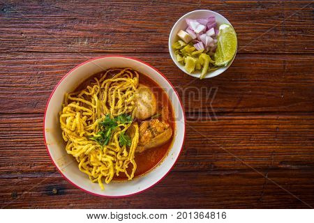 Khao Soi - Thai traditional food, noodles in curry soup with chicken on the wooden table. Khao Soi is a famous nothern part cuisine of Thailand. A closeup of Khao Soi in top view background.