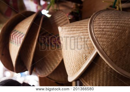 a traditional bamboo hat hanging on top java