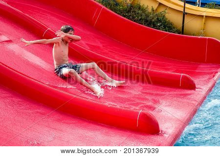Happy boy sliding on a water slide in aquapark