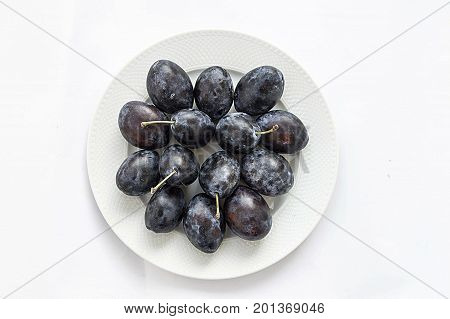 Black plums in a plate Black plums in different concepts in plates Natural and organic black plums in different concepts in the plate