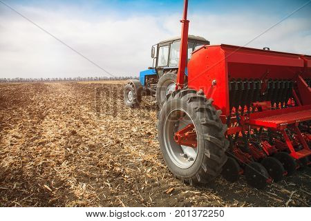 Modern tractor in the field with sowing complex. The concept of work in a fields and agriculture industry.