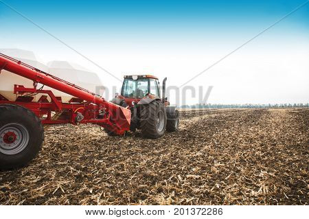 Tractor with tanks working in the field. Agricultural machinery and farming.