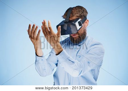 A young guy with a beard on a blue background in virtual reality glasses.