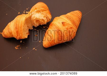 French Croissant with crumbs on black background