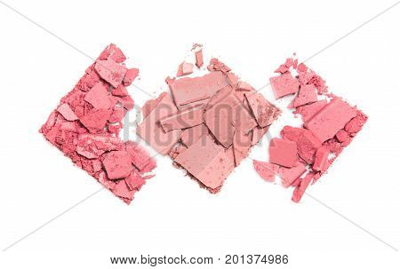 Pieces of scattered compact powder on white background in the form of three rhombuses