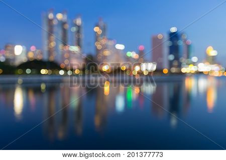 Blurred bokeh light with city office water reflection abstract background