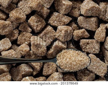 natural raw brown cane sugar cubes and granulated brown sugar in spoon close up as background. Top view of brown sugar with copy space