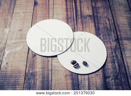 Photo of blank white beer coasters and coffee beans on wooden background.