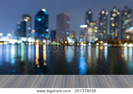 Opening wooden floor Night blurred bokeh light city downtown with water reflection abstract background