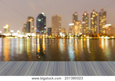 Opening wooden floor Blurred light night view city office building waterfront abstract background