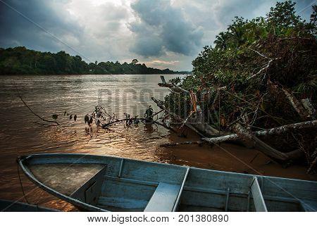 Kinabatangan River, Borneo, Sabah Malaysia. Evening Landscape Of Trees, Water And Boats.