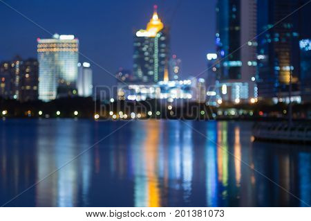 Blurred bokeh light office building downtown with water reflection abstract background