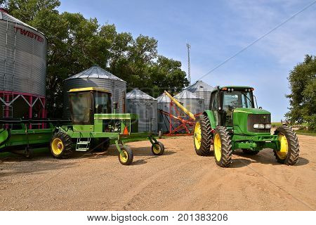 COMSTOCK, MINNESOTA, August 21, 2017: The John Deere 7320 and 2420  hooked up to grain elevators are products of John Deere Co, an American corporation that manufactures agricultural, construction, forestry machinery, diesel engines, and drive trains