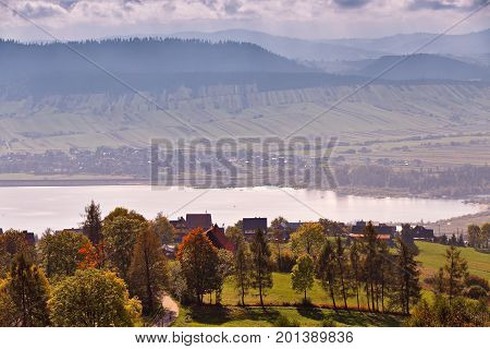 Lake Behind Foothills Of Tatra Mountains. Village On Lakeside