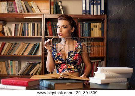 woman librarian in glasses sitting at the table studying book 1