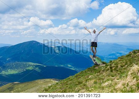 Young man tourist on cliff`s edge of mountains with hand up enjoy beautiful view of sky on top mountain. Travel and freedom concept
