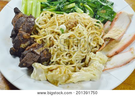 Chinese egg noodles topping slice barbecue pork and braised rib with dumping dressing sweet black sauce on plate