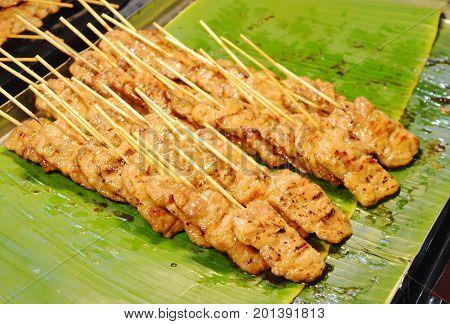 roasted fermented pork stabbing wooden stick on banana leaf in market