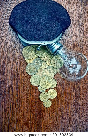 old leather wallet with coins and a light bulb on the table
