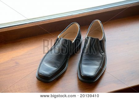 Man's Shoes Stand On A Window Sill