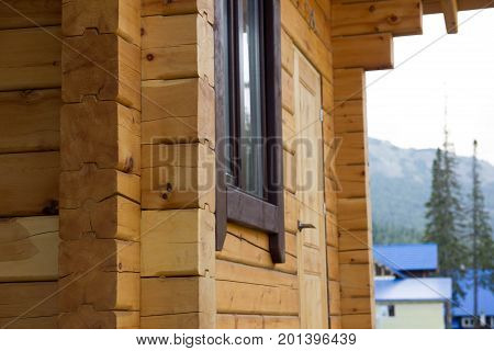 Wall background of the house made of timber covered with protective impregnation.
