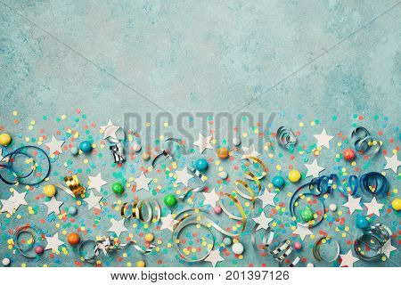 Holiday background decorated colorful confetti star candy and streamer on blue vintage table top view. Flat lay style. Festive border with copy space.