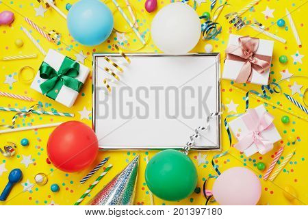 Party or birthday background. Silver frame with colorful balloon gift box carnival cap confetti candy and streamer on yellow table top view. Flat lay style. Holiday mockup. Greeting card with copy space.