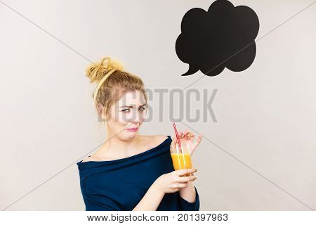 Disgusted blonde woman holding orange juice lady not enjoying fresh fruit drink black thinking or speech bubble next to her.