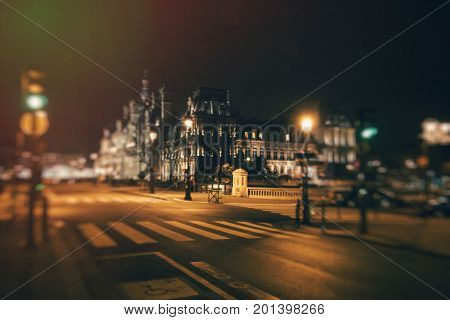 Crossroads and Hotel de Ville at night with tilt-shift effect. France. Paris