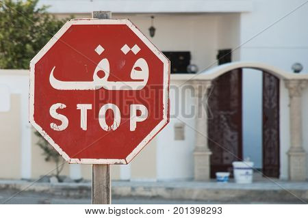 Red white bilingual Anglo Arabic octagonal stop sign on the street