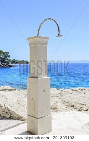 Beach outdoor shower on the background of the sea.