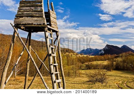 Meadow with hunting watchtower with mountain peaks in background,  Homolje mountains landscape on a sunny day in early spring, east Serbia
