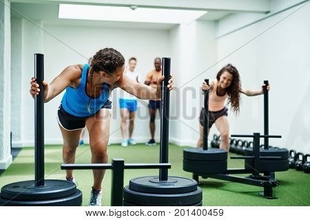 Smiling Female Friends Pushing Heavy Weights Together In A Gym