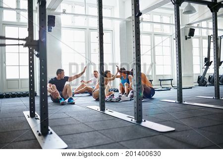 Smiling Friends Sitting On A Gym Floor High Fiving Together