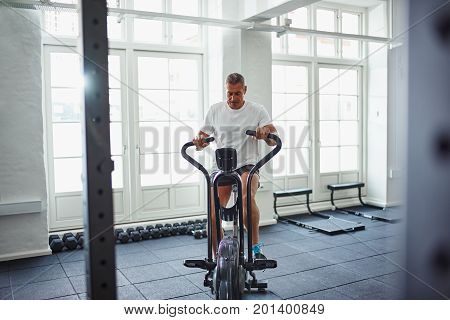 Fit Mature Man In Sportswear Exercising On A Stationary Bike