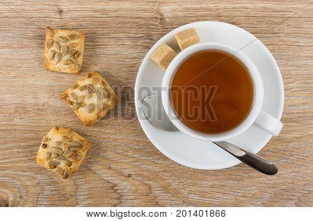 Tea, Sugar, Teaspoon And Cookies With Sunflower Seeds On Table