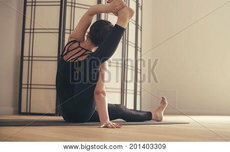 A young woman performing yoga-asanas in the hall. Eka pada shirshasana.