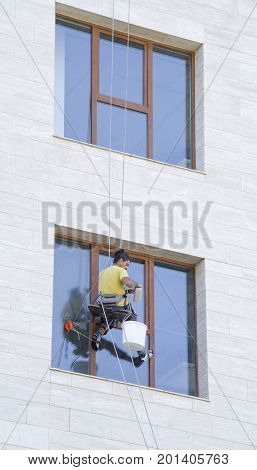 One window washer hanging on rope at work